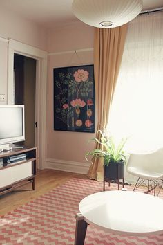 Living room from making it lovely: eames chair, nelson light fixture, media stand, botanical print, chevron rug, plant stand