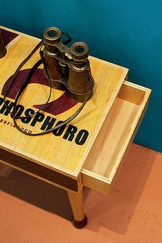 A mesinha de madeira tem o formato de uma embalagem de caixa de fósforos que até abre. O compartimento serve para guardar objetos que devem ficar escondidos