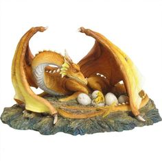 The Brood - A yellow dragon protecting her eggs with her wings gazing upon a new born hatchling. Beautifully hand painted and made of cold cast resin. Approx. 21 cm. A Nemesis Now product.