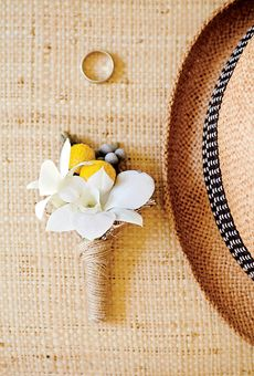 Beach boutonniere of orchids and craspedia wrapped in twine..