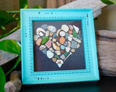 """Handcrafted unique hearts featuring genuine sea glassthat was hand picked from the beach. The powerful mysterious sea created each piece.  The hearts are made up of genuine pieces that have come from the water, and have not been altered.  Permanently mounted on a piece of light blue cardstock. A 11""""x 11"""" clean white frame encases the beautiful hearts. The frame comes with a hook for displaying or could be mounted on an easel."""