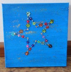 canvas in gewenste kleur schilderen, ster overtrekken en lijn met kraaltjes, pailletjes en dergelijke 'borduren'