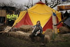 A man plays the accordion as he sits outside a tent in a protest camp set up close to the entrance of the IGas exploratory gas drilling site at Barton Moss, near Manchester, northern England, March 6, 2014. REUTERS/Phil Noble