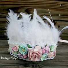 Welcome to Vintage Fairy This lace crown is simply stunning, featuring stunning soft white feathers, lovely white lace with designer gathered fabric and then gorgeous pastel flowers in soft blues and baby pink. Lovely beads scattered through the flowers, this is a lovely headpiece which can be used for many occasions, photo props, weddings, fairy parties, beach themes etc. Ties in the back with ribbon . Fits newborn up to adults