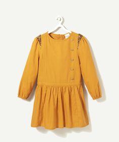 LA ROBE HORQUE :                     Avec ses détails strass et boutons, cette magnifique robe a tout pour avoir un look chic et branché ! Les filles vont l'adorer !            LA ROBE HORQUE, col rond, manches longues, forme évasée, boutons fantaisies, bas de manches élastique, ouverture zip dans le dos, strass au niveau des épaules, imprimé.