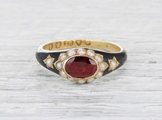 Antique Georgian mourning ring made in 18k yellow gold and black enamel. Centered with an oval rubellite and accented with seed pearls. Engraving reads Dear Father ob: April 18th, AE:59. Circa 1790 England.