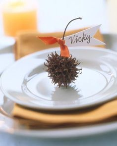 Cute place cards - a sweet gum tree spur with name tag attached - via Martha Stewart