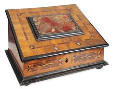 MID-18TH CENTURY VIENNESE SEWING BOX WITH ORIGINAL NEEDLEWORK CUSHION  The slant-top sewing box of elaborate inlay designs on top and sides,has flattened ball-feet,cast ball studs,and a large framed needlework pincushion centering the lid. The entire interior is covered with hand-painted paper with raised design and there is a marquetry wood panel with floral design at the center inside lid. Vienna,Baroque era,circa 1750.