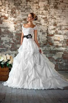 D1239  This lace over Soft Organza ball gown features a sophisticated crystal embellished bodice and layers of eye-catching fabric pickups and lace appliqués on the skirt. Detachable shawl included. Choose from a corset or zipper closure. Satin beaded belt also sold separately.