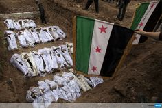 """SYRIA, ALEPPO : Syrian mourners wave the pre-Baath Syrian flag, now used by the Free Syrian Army, over the bodies of civilians, who were executed and dumped in the Quweiq river, during their burial at a park now renamed """"Martyrs of the River"""" park in the Bustan al-Qasr district of the northern city of Aleppo on January 31, 2013. AFP PHOTO/JM LOPEZ"""