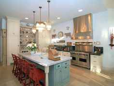 Blue cabinetry and red stools pop in this country chic kitchen. #interiordesign #decor #home