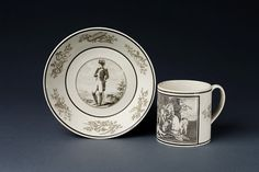 Cylindrical coffee mug with loop handle printed in black with a panel with bacchanalian scene after Poussin and with trophies, the saucer printed with a full length portrait of Napoleon and with a border of trophies. Creil factory, 1808-18.