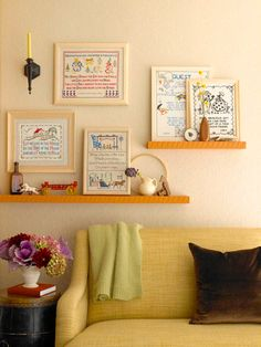 Cross-stitched Wall Art  Turn vintage cross-stitched samplers into a unique and homespun wall display. Place some on floating shelves and hang a few on the wall. Use similar frames for the samplers to create a unified display.