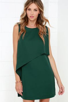 """We've got a """"whole lotta love"""" for the Give a Little Love Dark Green Dress! Silky woven poly fabric begins at a high, rounded neckline that fastens at back with an exposed gunmetal zipper. Sleeveless shift silhouette is accented by a fun asymmetrical ruffle that drapes from the neckline to the short hem. Fully lined. 94% Polyester, 6% Spandex. Dry Clean Only. Imported."""