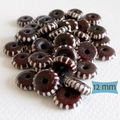 Dark Brown Bone Beads Line Pattern  Bead Size: 12 mm dia. X 4 mm, with 3 mm holes (US penny = 19 mm dia.)  Material: Bone  Quantity: Purchase 24 beads for $3.85  Batik beads are recognizable by their contrasting (black and white or brown and white) patterns. They undergo a wax resist treatment that has been in use since the 4th century (Many of us are familiar with batik fabrics, made using a similar process.) First, wax is applied to areas that will remain white, then beads are submersed in…