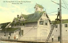 "1911 post card shows the O.C. Life-Saving Station at its original location on Caroline Street. Each Monday and Thursday the keeper and the surfmen at the station were required to perform the breeches buoy drill using the ""wreck pole"" outside the station. Sometimes during the summer months a lucky visitor would be invited to participate in this exercise by serving as a ""shipwreck victim"" and riding in the breeches buoy."