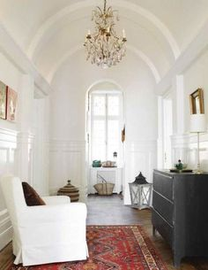 I like the mix of materials.  Chandelier, white walls and chair, straight-lined cabinet, natural basket and rustic lamp.  And bright rug.