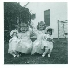 Vintage snapshot / photo of two little girls holding matching dolls, 1954.