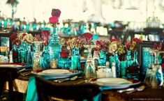 Bohemian Tablescape with mixed turquoise glass bottles & mercury glass in Turquoise, Red & Teal with~ green and burgundy hydrangeas, mauve cymbidium orchids, red garden roses, red dahlias, & fuschia cockscomb