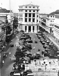 Raffles Place, circa 1934.  A hill originally stood at where Raffles Place is. Its soil was used to reclaim the southern bank of the Singapore River to form Boat Quay. Known as Commercial Square then, Raffles Place was no more than a quiet green when it was first developed from 1823 to 1824. As the economy of Singapore grew, two- and four-storey buildings sprang up around the square, housing mercantile offices, banks and trading companies.  In 1858, Commercial Square was renamed Raffles…