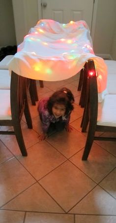 Fun for a rainy day: use Christmas lights, a sheet, and chairs to create this tunnel.