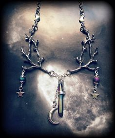 A one of a kind handmade necklace with an enchanted forest theme. This necklace features sturdy tree branch connectors made from antiqued silver plated metal alloy (lead and nickel free pewter base). Hanging from these branches on each side are little star charms accented at their tops with rainbow titanium quartz druzy beads. The beads have decorative silver beads caps. The pendant that hangs from the bottom center is a wire wrapped rainbow titanium quartz crystal measuring a little over an…