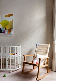 Clean and spare nursery with Stokke cot  and art by Michael Muir. Photographs by Sean Fennessy, styling / production by Lucy Feagins / The Design Files.