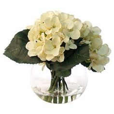 "Featuring faux hydrangeas in a glass bubble vase, this lovely arrangement brings a touch of natural style to your decor.   Product: Faux floral arrangementConstruction Material: Silk, plastic, acrylic and glassColor: Cream and greenFeatures: Includes faux hydrangeasDimensions: 9"" H x 9"" Diameter"