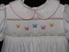 Smocked with pastel butterflys on the front.  Made of White Satin Batiste. Fabric has a beautiful sheen.  Piped in printed pink piping on front yoke, back yoke, collar, and sleeve cuffs.  Ties in back with sash and closes with three heart shaped mother of pearl buttons.