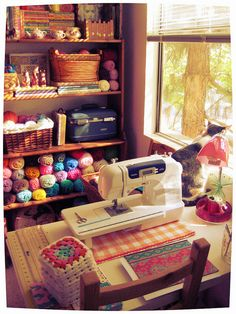 so in love with this room: yarn, granny squares, craft stuffs, wooden rack, and of course, a cat
