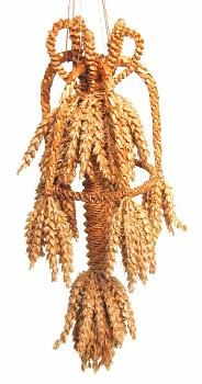 This corn dolly, called the 'Charlbury Crown', was designed by Anita (Jo) Dunn and made by Alec Coker. It consists of spirally woven central core with corn ears at the top and bottom, and a spirally woven circle surrounding the middle of the core. Five plaited bands are attached to the top of the core at one end and the circle at the other. Five plaited loops are attached to the top of the dolly for decoration.  (MERL/86/130)