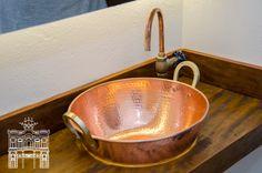 Criatividade em cobre. Tacho vira cuba, cano e registro viram torneiras e tudo vai bem em uma bancada de madeira de demolição. As peças estão no em uso no toalete da Casa da Bóia.
