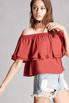 A crepe woven top by Lush™ featuring an off-the-shoulder neckline, tiered flounce construction, short sleeves, and a boxy silhouette.