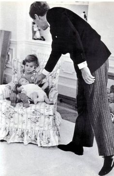 Caroline holding her new baby brother john f. kennedy jr while their father says hello at the winter home in palm springs.
