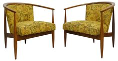 Pair of Danish-style walnut barrel-back lounge chairs. The chairs feature open upholstered backs, round tapered sculptural legs, continuous armrests, and newer upholstery. No maker's mark. Seats,...