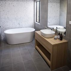 Timber vanity with white free standing basin, white free standing bath tub, chrome tap and mixer, dark grey tile flooring. Project by - @finewooddesignerkitchens #taps #interiordesign #bathroom #australia #architecture #bathroomdesign #bathroomcollective Visit our website for more www.bathroomcollective.com.au