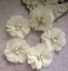 This lot of five chiffon flowers are perfect for all your DIY needs. A beautiful ivory colored chiffon is adorned with rhinestones and pearls. These flowers are perfect for headbands, maternity sashes, and everything in between. Approximately 2 inches