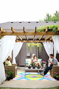 pergola moderne autoportée en bois décorée de rideaux blancs, tapis en couleurs vives et coussins extérieurs