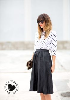 Estilo ladylike: Super feminina, a saia midi plissada ficou linda quando combinada a uma camisa de branca de bolinhas pretas! Um clássico que nunca erra! Para deixar o visual mais informal – mas não menos fashionista – o modelo dobrável da clutch de oncinha.