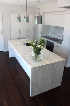 My Kitchen - Carrara Marble waterfall benchtop and splashback, Copacabana pendants and fully integrated appliances. #design #interiors #kitchen #home #interiordesign #marble