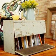 An old kitchen cabinet gets new life as a side table and bookcase. Turn the cabinet on its side for easy access to the books. If the cabinet does not have a lock, add one to keep doors closed when necessary