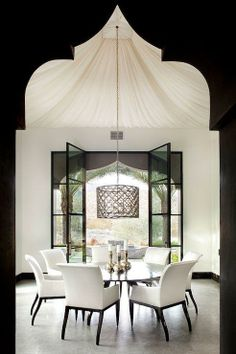 We are loving the minimalist feel of this chic Moroccan style dining room. The black quatrefoil drum pendant is the focal point of the space and creates a dramatic and elegant finish touch to the space. Here's a tip - If you decide to go with a large drum pendant such as this one and are planning on installing it in a space that has large windows or glass doors, you may want to center your new fixture in front of the window for maximum curb appeal and aesthetics.