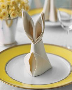 """Easter-rabbit-shaped napkins are a festive detail for the holiday table, and they only require a few simple folds. Well-starched crisp cotton or linen will transform into the sturdiest bunnies. Fold napkins the day before your meal so your """"warren"""" is full when guests arrive."""