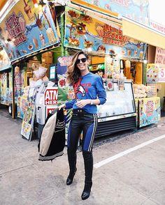 Look Camila Coutinho no desfile da Tommy: moletom e calça azul, bot over the knee preta e casaco da Tommy