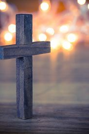 A wooden christian cross with a soft bokeh lights background pic.