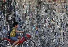"Wall of phones: ""A boy cycles past a wall of mock-up mobile phones displayed outside Wataden electronics store in Tokyo's Edogawa Ward on Thursday. The store owner started this display with a few thousand cell phones 10 years ago."""