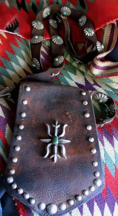 Early 1900's Navajo Bandolier Bag. This is the earliest silver mounted bandolier bag I have offered for sale. With 55 silver buttons and a wonderful heavy sandcast stamped leaf and green turquoise central Ketoh-like design, this is truly an iconic piece of Navajo workmanship.