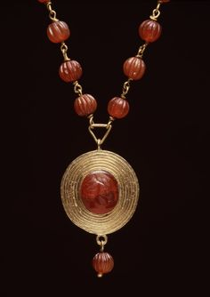 1st century BC-AD 1st century (Imperial (Roman) (?))  gold, carnelian. Necklace with Child's-Head Pendant. This necklace is a pastiche. The carnelian beads are ancient and strung on modern gold links. The lion-head finials comprising the hook and eye clasp are reused from Greek earrings. The child's head boldly carved in a carnelian stone is set in a gold setting, which may or may not be ancient.