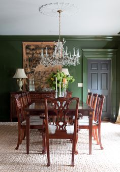 A bold dining room. The crystal chandelier looks especially dramatic against the lacquered emerald walls when its lit. R. Higgins Interiors