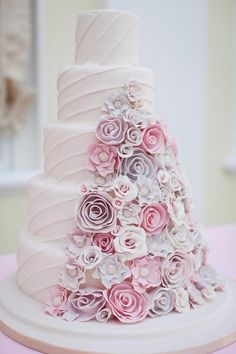 Pink and purple wedding cake with flowers..The Cheryl cake has a pyramid of pretty floral detailing which leads the eye up to the top of the cake. Make the most of this by picking a unique wedding cake topper to add the perfect finishing touch.